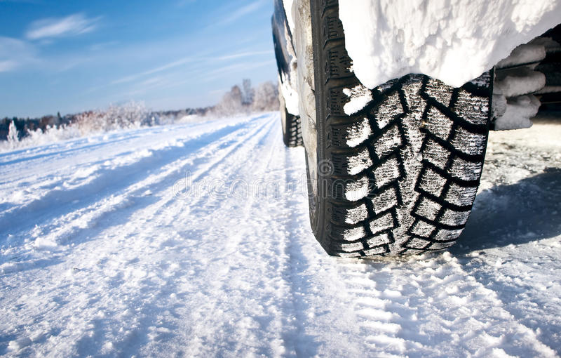 Car tires on the road. Closeup of car tires in winter morning royalty free stock images