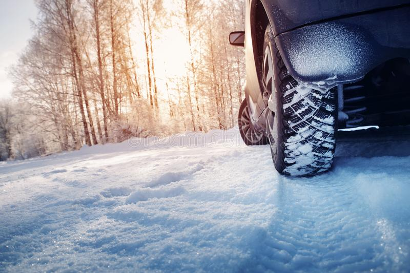 Car tires on winter road covered with snow. Snowy landscape with a vehicle stock photography