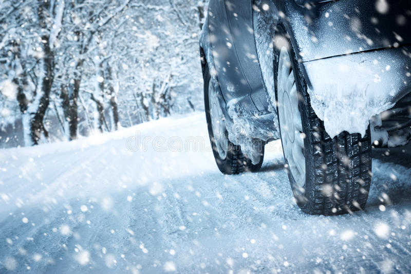 Car tires on winter road stock photography
