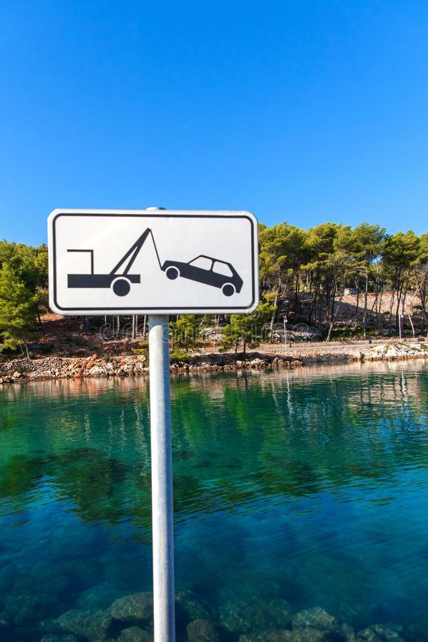 Car towing sign by the sea. Street sign of a car being removed in white color. No stopping clearway car tow warning sign. royalty free stock photos