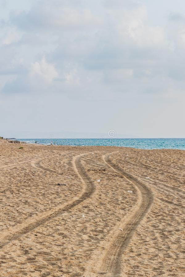 Car tracks on the sand going to the sea. Vertical shot. Nature landscape. Summer time. Point of horizon.sinuous tracks stock photography