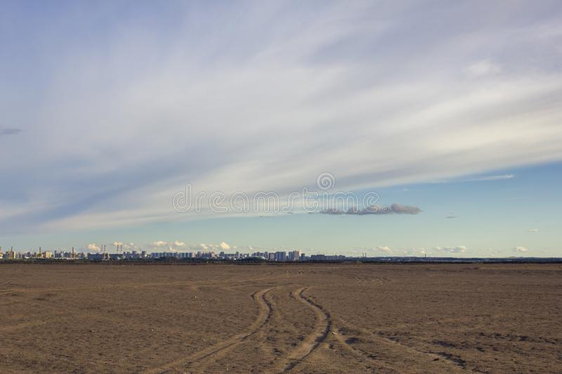 Car tracks in the sandy desert on the background of a modern city with pipes of factories under the blue sky. A car tracks in the sandy desert on the background royalty free stock photography