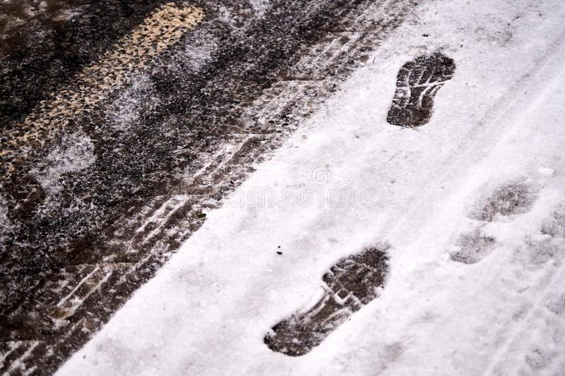 Car tracks and shoe footprints in snow. On icy winter road. Winter background theme royalty free stock photo
