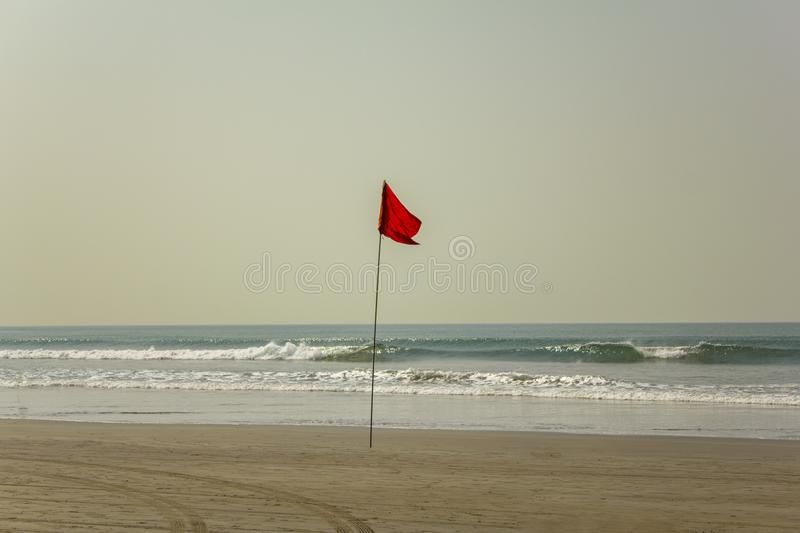 Car tracks on a yellow sandy beach near a red flag prohibiting swimming amid ocean waves under a clear blue sky. A car tracks on a yellow sandy beach near a red stock images
