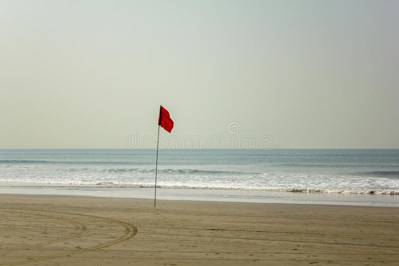 Car tracks on a yellow sandy beach near a red flag prohibiting swimming on a background of blue ocean under a clear sky. A car tracks on a yellow sandy beach royalty free stock images