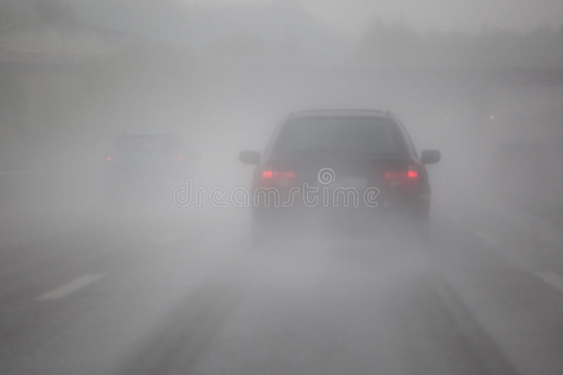 Car traffic with fog and rain stock image