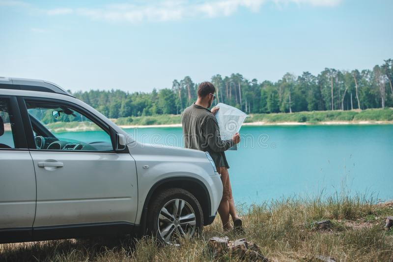 Car travel concept man looking on the man at suv car hood lake on background royalty free stock photos