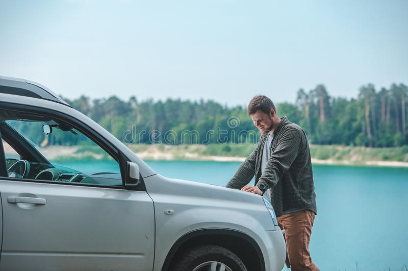 Car travel concept man looking on the man at suv car hood lake on background stock photo
