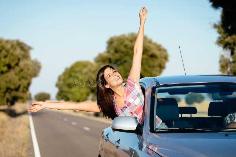 Car travel freedom. Blissful woman on car travel raising arms. Happy brunette girl enjoying freedom on roadtrip vacation stock image