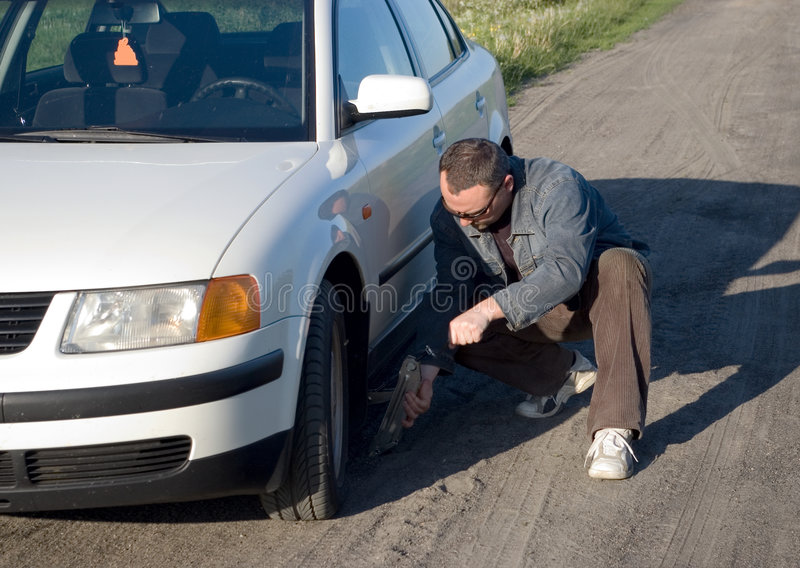 Car trouble. A man with a lever in his hands bent at a white car, country road stock image