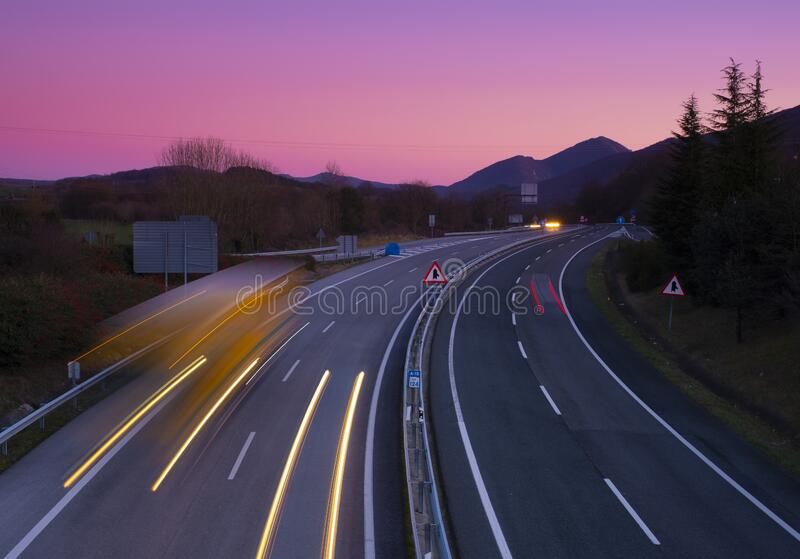Car and truck lights at sunset on a road in Navarra stock photography