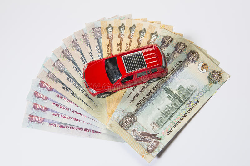 Car and UAE Dirham. A red toy car on the stack of UAE Dirham notes stock images
