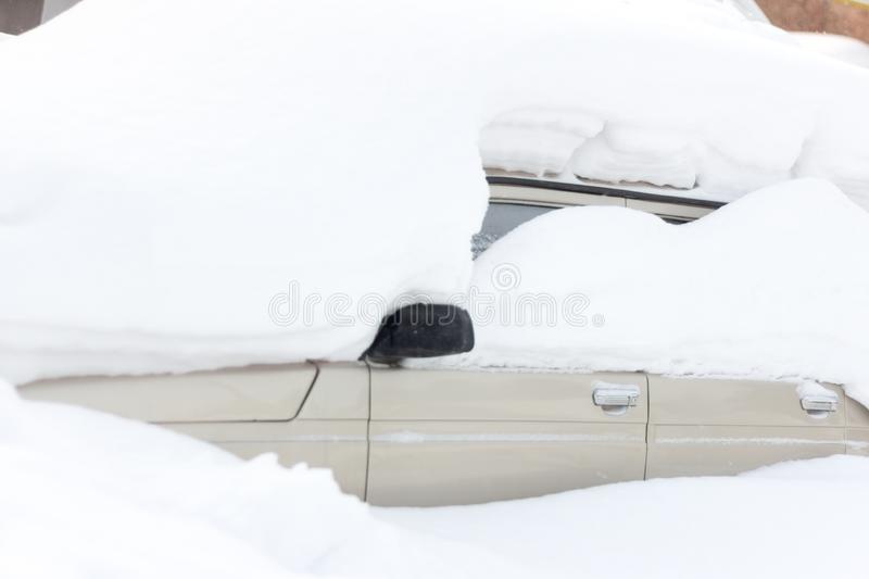 Car under the snow. A lot of snow fell on the street.The car is completely covered with snow after heavy snowfall stock photography