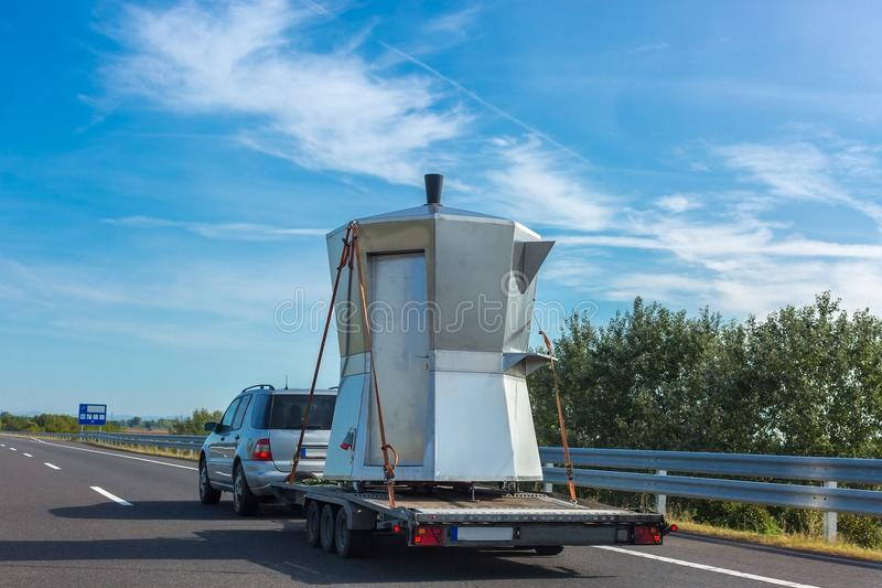 Car with unusual kiosk in the form of Espresso Coffee Maker Moka Pota on a trailer on the highway. On sunny day royalty free stock photo