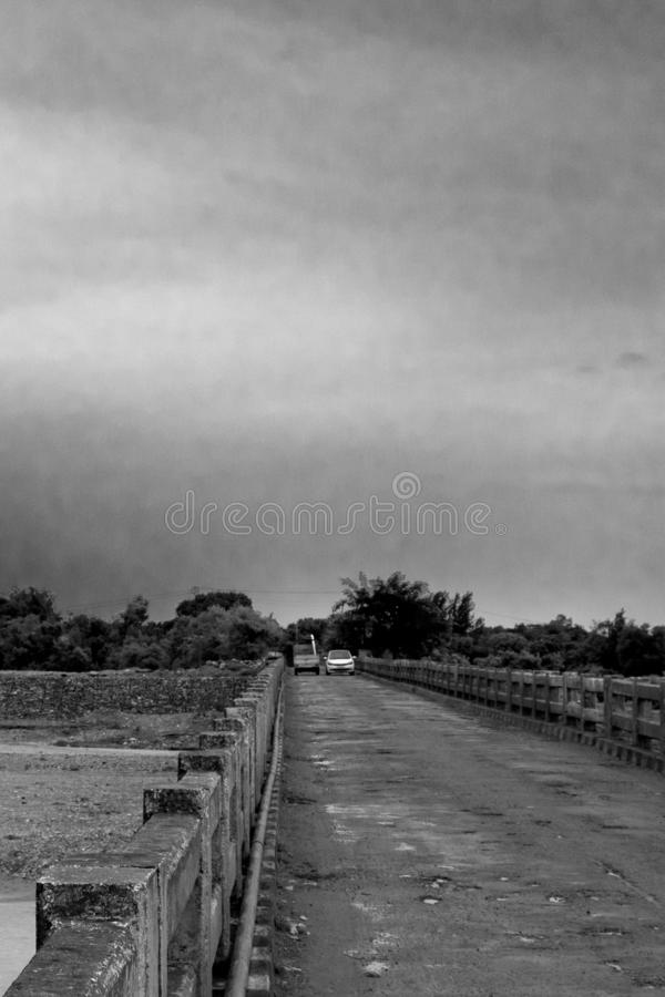 Car and Van Goes Through an Old Bridge. Blank and White Old Bridge royalty free stock image