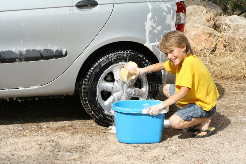 Car wash. Little boy with soapy sponge washing a car royalty free stock photo