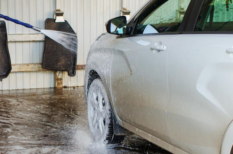 Car wash from spray gun with foam aimed at the car wheel stock images