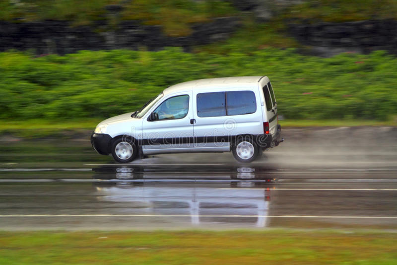 Car on wet road. On high speed stock photography