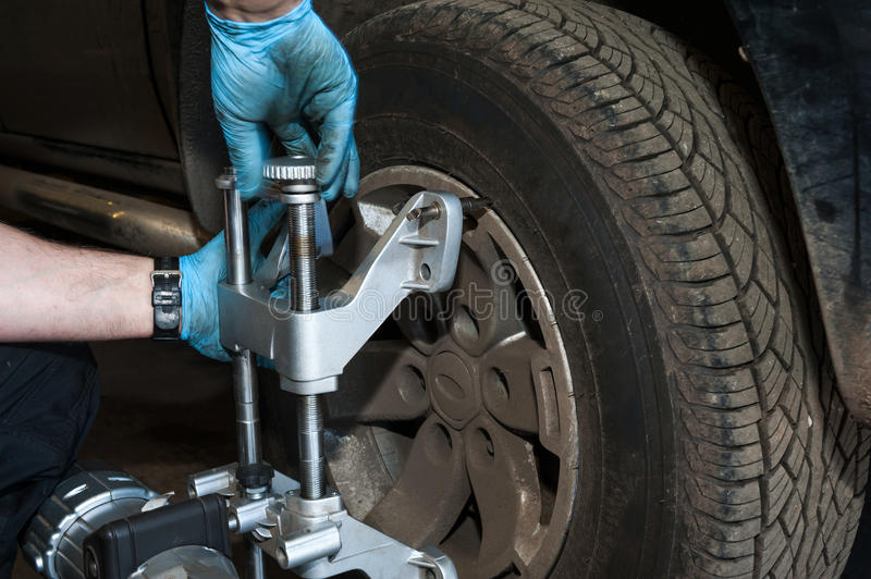 Car wheel alignment details. Close-up of a car mechanic checking a wheel alignment royalty free stock images