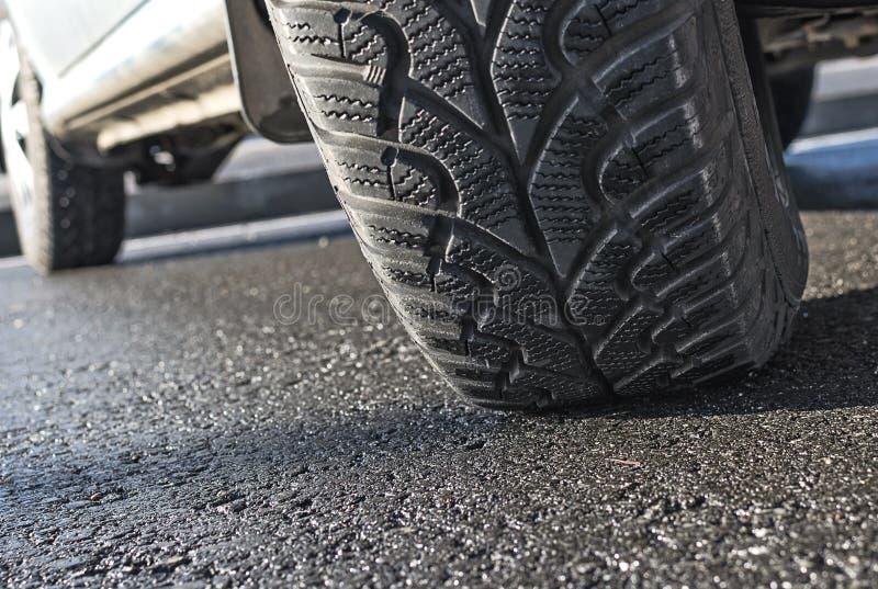 Car wheel on asphalt closeup. Car wheel on wet asphalt closeup royalty free stock photos