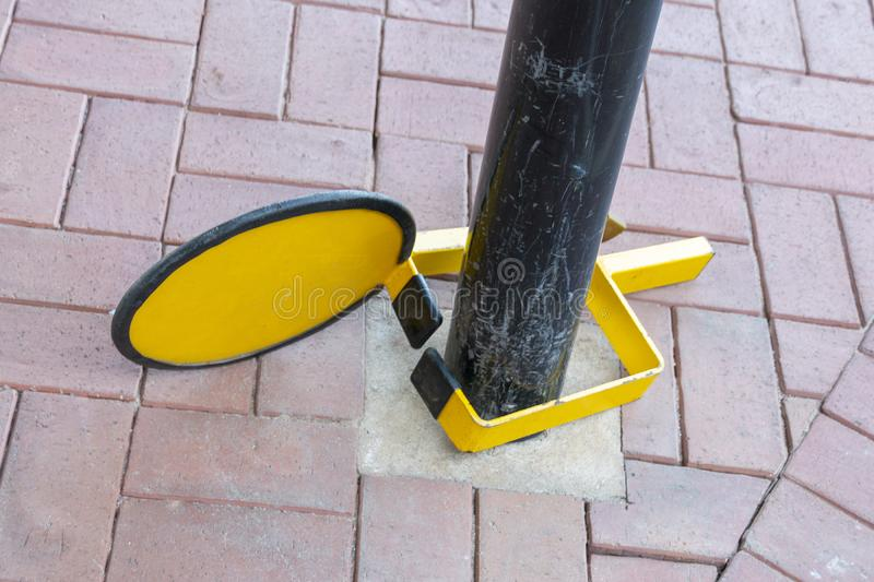 A Car Wheel Clamping Device. A close up back view of a yellow and black car wheel clamping devise locked to a pole next to restricted parking area royalty free stock photo