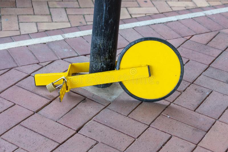 A Car Wheel Clamping Devise. A close up front view of a yellow and black car wheel clamping devise locked to a pole next to restricted parking area royalty free stock photography