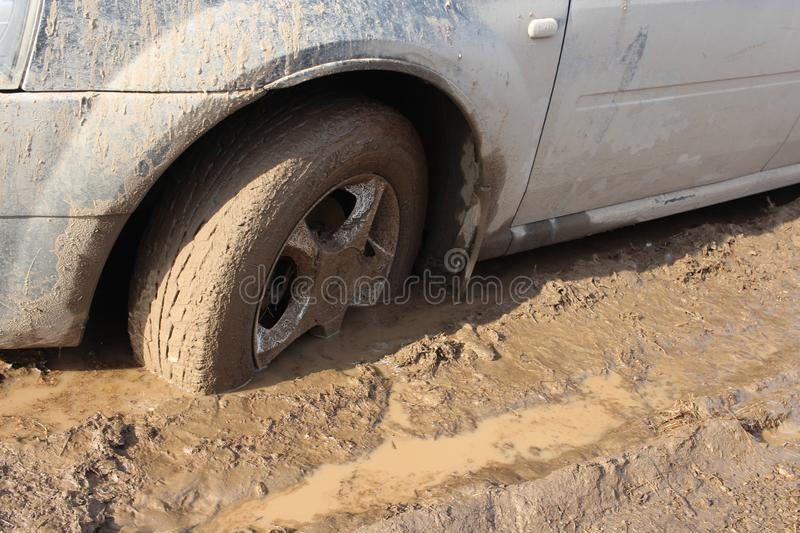 Car wheel stuck in mud slips in a puddle on the road royalty free stock images