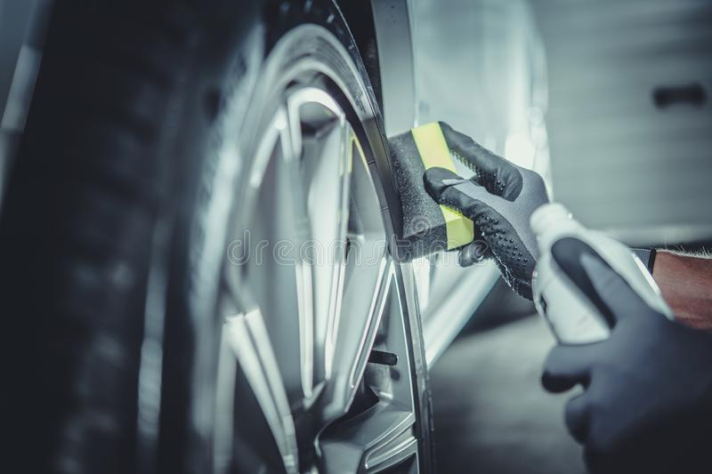 Car Wheel and Tires Cleaning. And Protecting by Professional Vehicle Detailing Cleaner royalty free stock photo