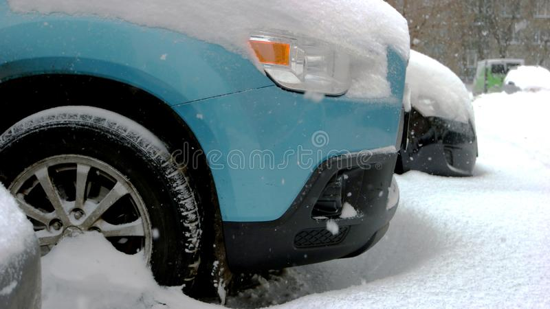 Car wheels stuck in snow drift. Wheel of blue passenger car is stuck in snow. Adverse weather conditions royalty free stock photography
