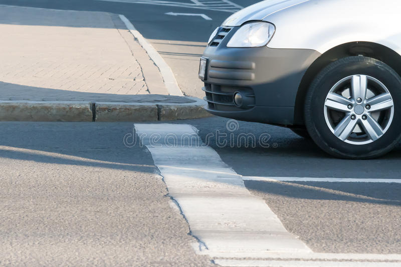 The car which has stopped forward wheels before the stop line. In summer day stock image