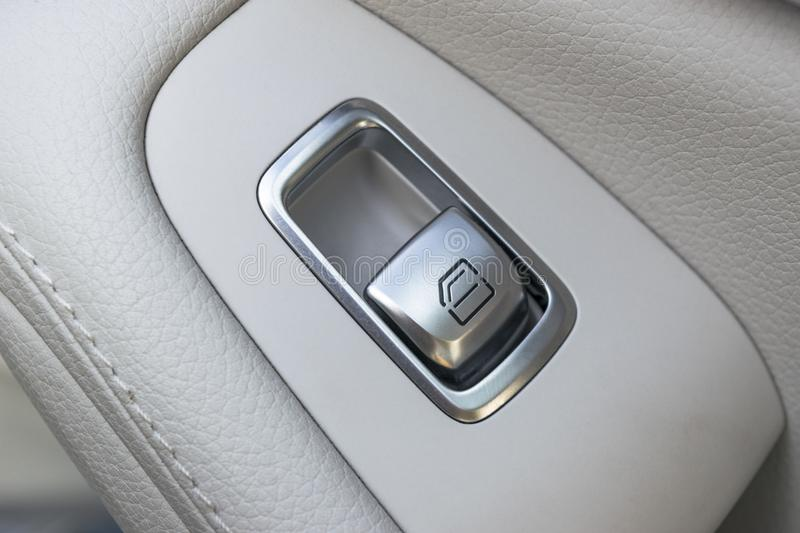Car white leather interior details of door handle with windows controls and adjustments. Car window controls of modern car.  stock image