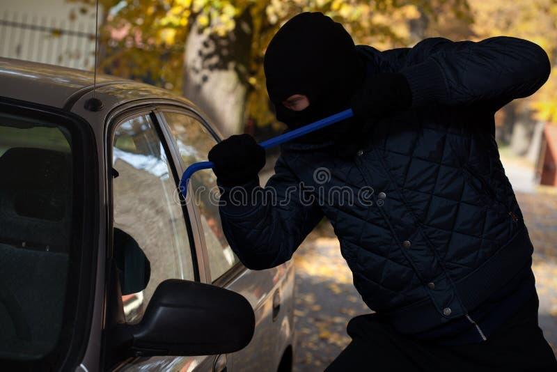 Car window break-in. A man breaking in a car through its window royalty free stock photo