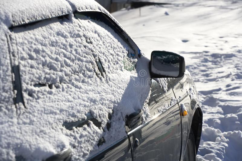 Car Windows are covered with a layer of snow. Close - up of the car after a snow storm stock images