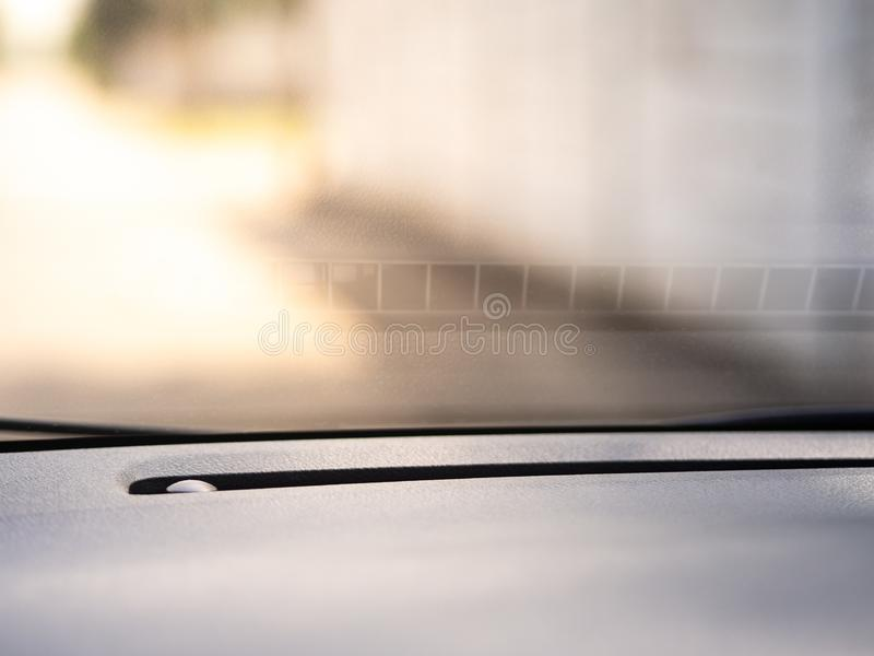 Car windshield and console textures with yellow sunlight. Closeup car windshield and console textures with yellow sunlight royalty free stock image