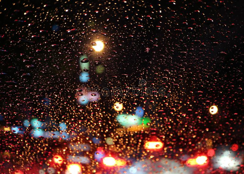 Car windshield full of raindrops with blurry traffic jam on the urban street at night stock image