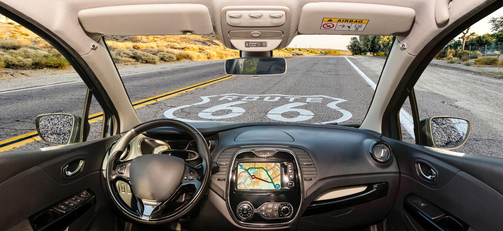 Car windshield with Historic Route 66 sign in California, USA. Looking through a car windshield with view over the Historic Route 66 and pavement sign in stock photography