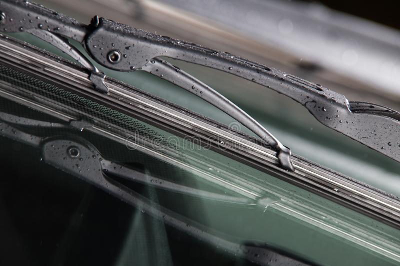 Car windshield wiper. Closeup. New car wiper with raindrops royalty free stock photography