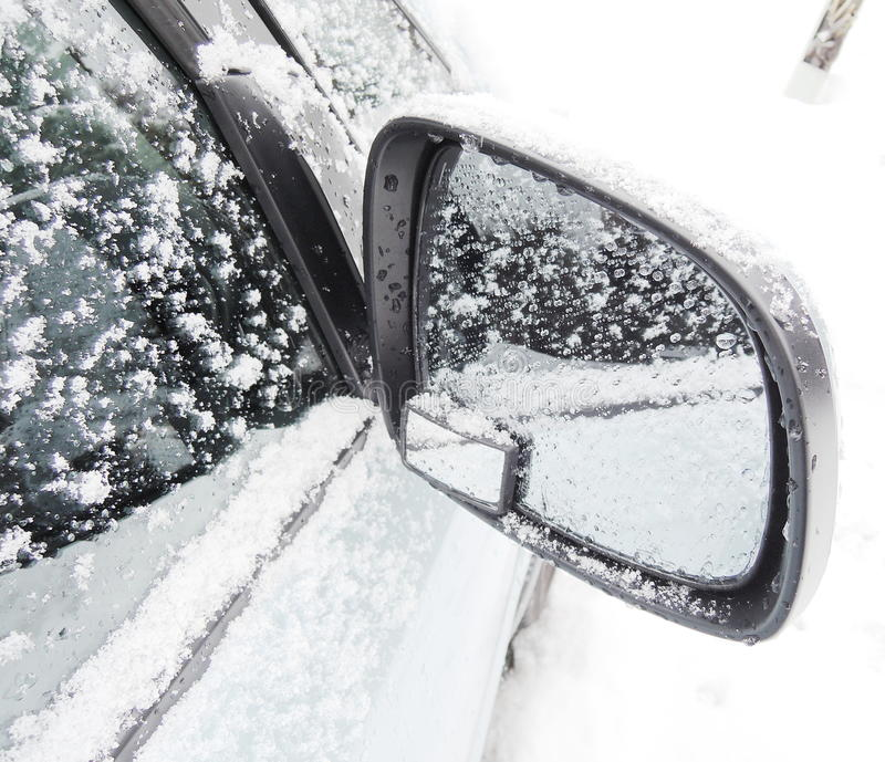 Car wing mirror. All covered up with snow stock photo