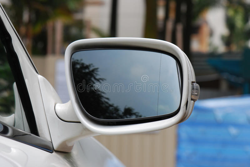 Car Wing Mirror. A photo taken on the side wing mirror of a light coloured luxury car stock image