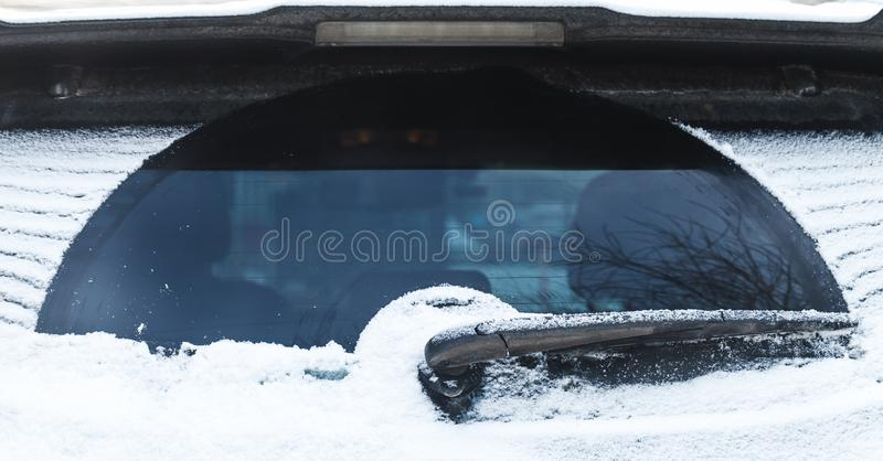 Car wiper on rear window covered with snow. Car wiper on rear SUV window covered with snow in cold winter season stock photos
