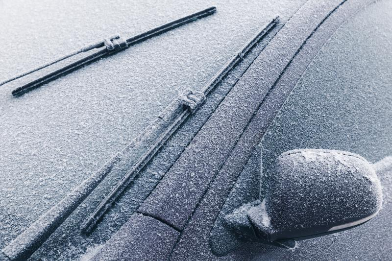 Car wipers on frozen windshield and mirror stock images