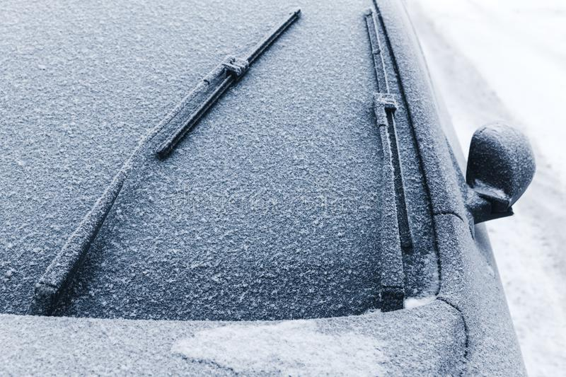 Car wipers on windshield covered with snow. In cold winter season stock photography