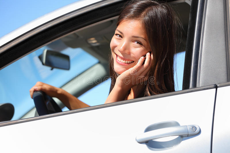 Car woman using smart phone. While driving in car. Beautiful young woman talking on mobile phone smiling happy looking at camera. Mixed race eurasian woman stock photography