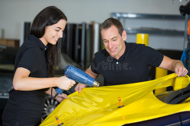 Car wrappers using heat gun to prepare vinyl foil stock photography