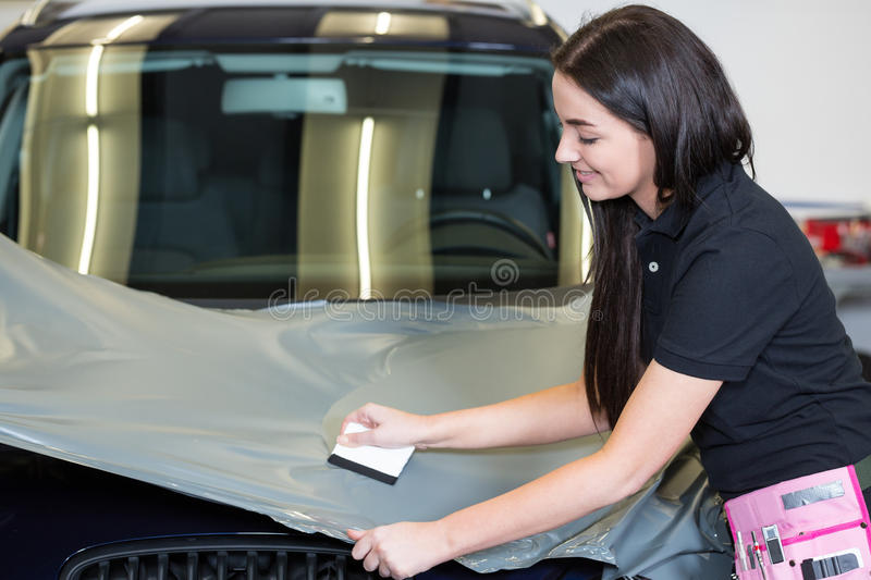 Car wrappers using squeegee to straighten vinyl film. Car wrappers using squeegee to straighten vinyl foil stock photography