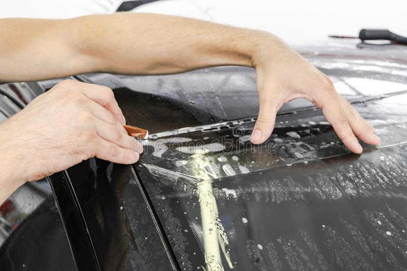 Car wrapping specialist cutting vinyl foil or film on car. Protective film on the car. Applying a protective film to the car with. Tools for work. Car detailing royalty free stock photos
