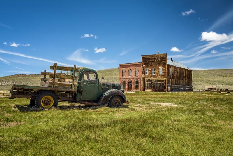 Car wreck in Bodie ghost town, California. Car wreck and old buildings in Bodie ghost town, California. Bodie is a historic state park from a gold rush era in royalty free stock image