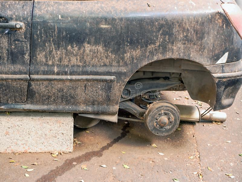 A car wreck built on stones in former dark blue or black, the wheels are dismantled stock photography