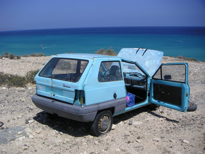 Car wreck on sea beach. Wrecked blue car on the beach, blue ocean & sky. Playa Calma, Fuerteventura stock images