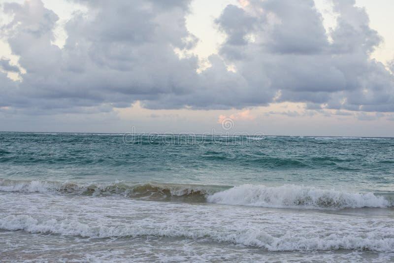 Caraïbisch strand met turkoois water en donkere wolken stock afbeeldingen
